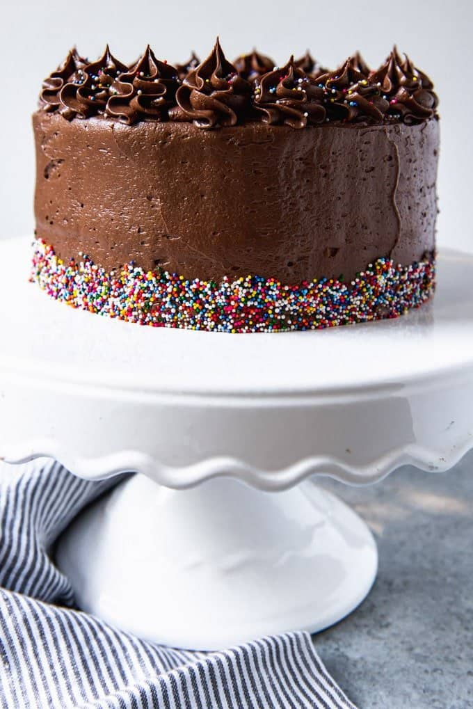An image of a yellow cake frosted with chocolate buttercream frosting and sprinkles on a white cake stand.