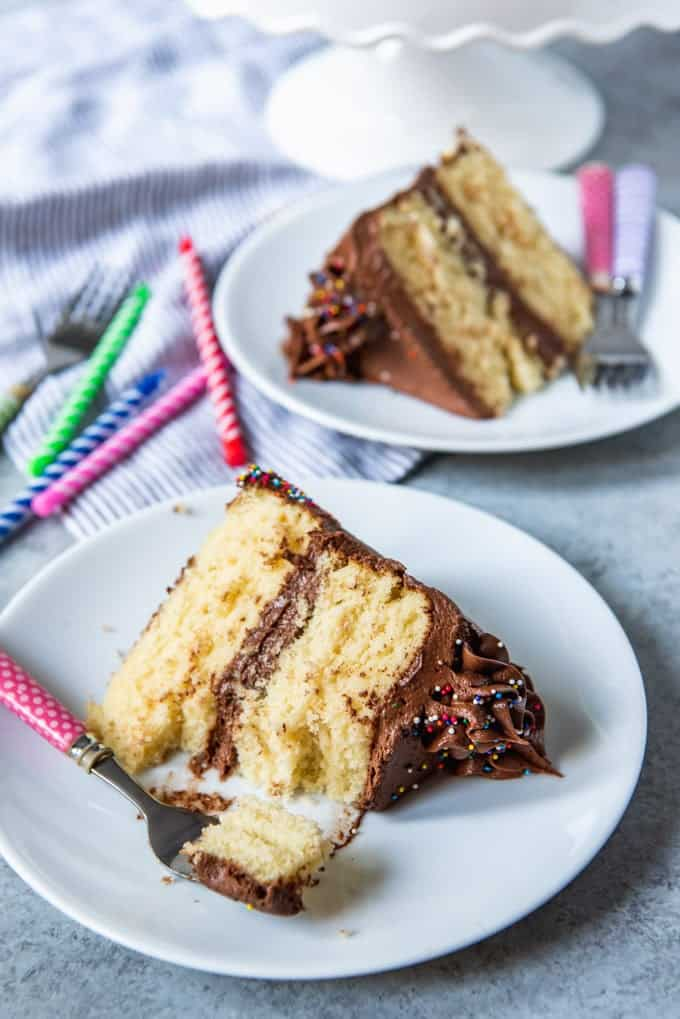 An image off two slices of yellow birthday cake with chocolate frosting with a bite taken out of one piece and candles beside it.