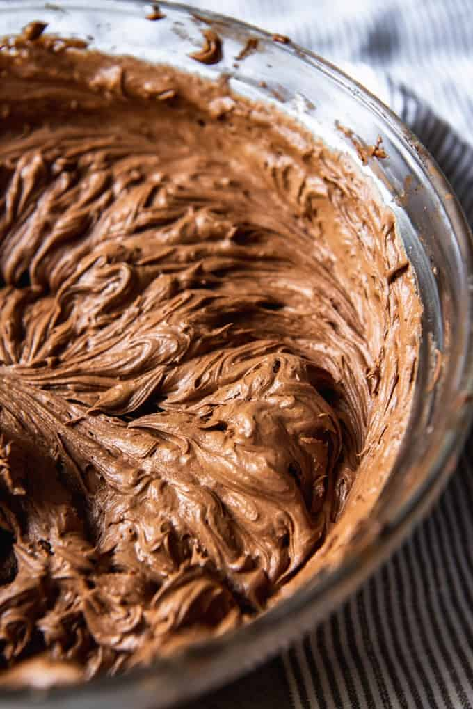 An image of a bowl of chocolate buttercream frosting for yellow cake.