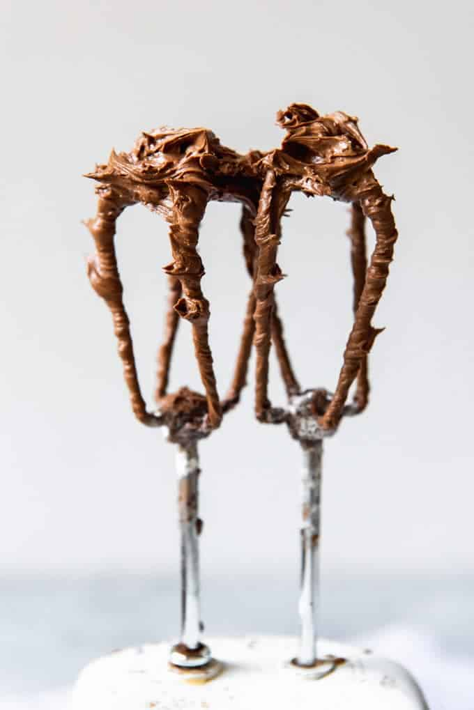An image of two beaters with chocolate buttercream frosting on them.