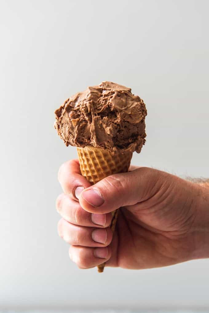 An image of a hand holding a sugar cone with a scoop of chocolate burnt almond ice cream.