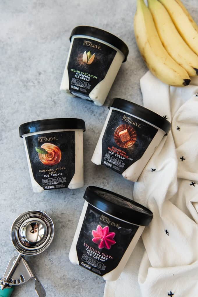 An image of four containers of ice cream from the Safeway Signature Reserve Premium Ice Creams line, including Indian Cardamom Pistachio, Caramel Apple Chai, Bourbon Maple Blondie, and Brazilian Guava Cheesecake.