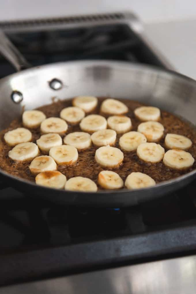 An image of sliced bananas in a pan with butterscotch sauce.