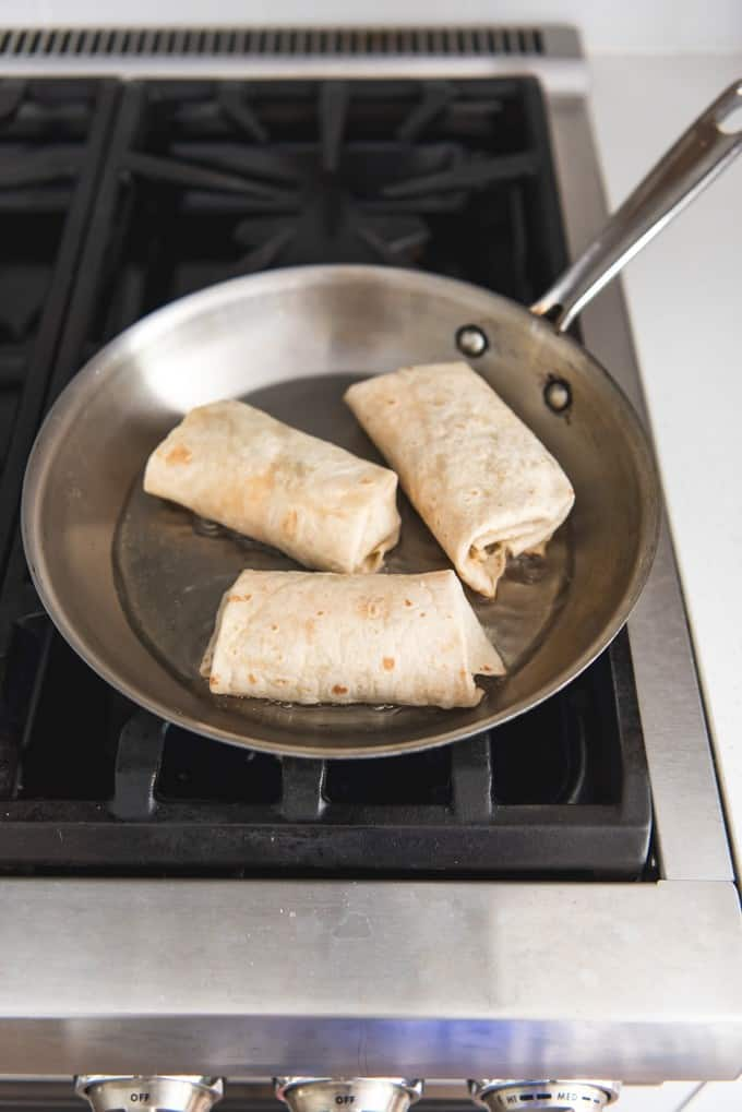 An image of three chicken burritos frying in a pan in oil to make homemade chimichangas.