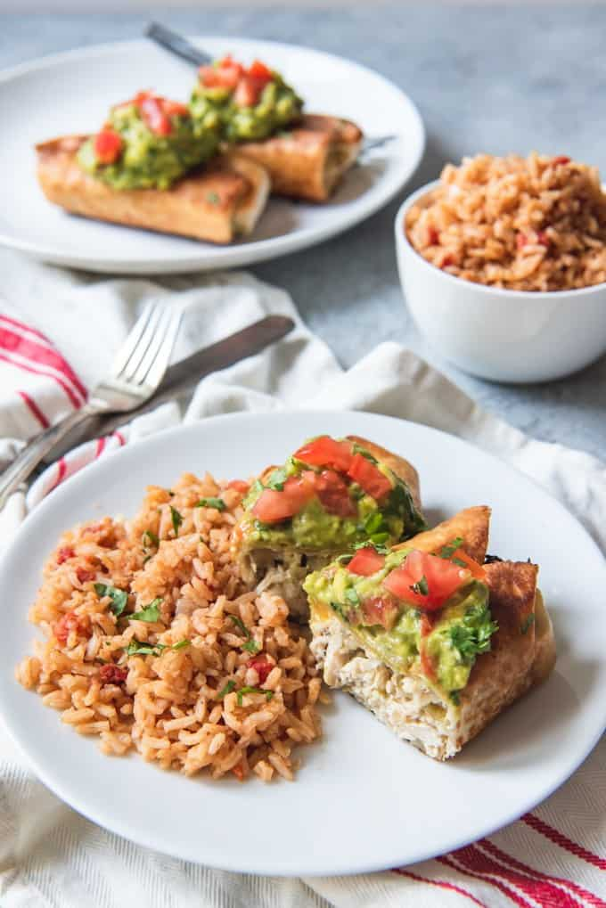 An image of a chicken chimichanga that is cut open and served with Mexican rice.