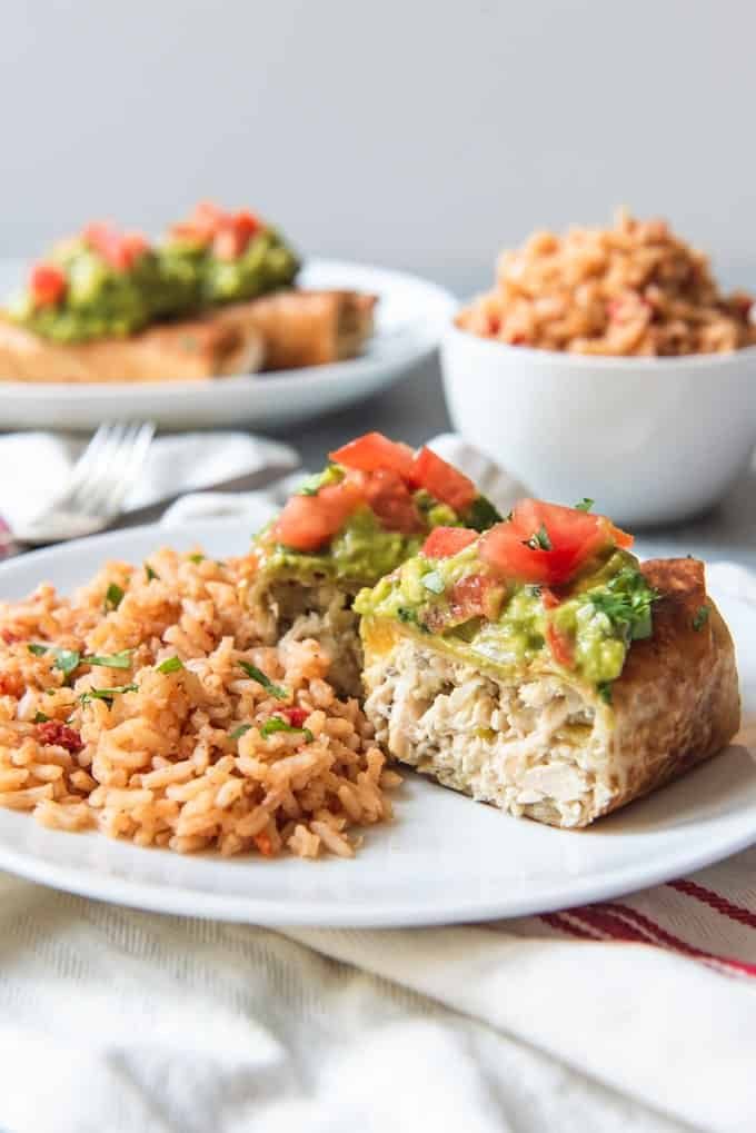 An image of a chicken chimichanga sliced open and served with Spanish rice.