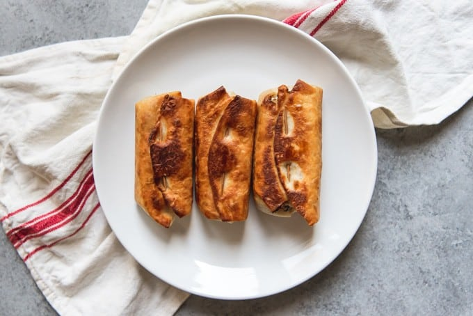 the bottoms of three cooked Chimichangas on a white plate