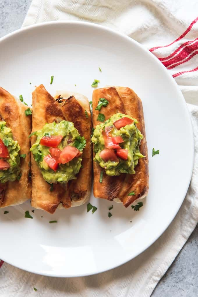 An image of a white plate with three chicken chimichangas topped with fresh guacamole and chopped tomatoes.