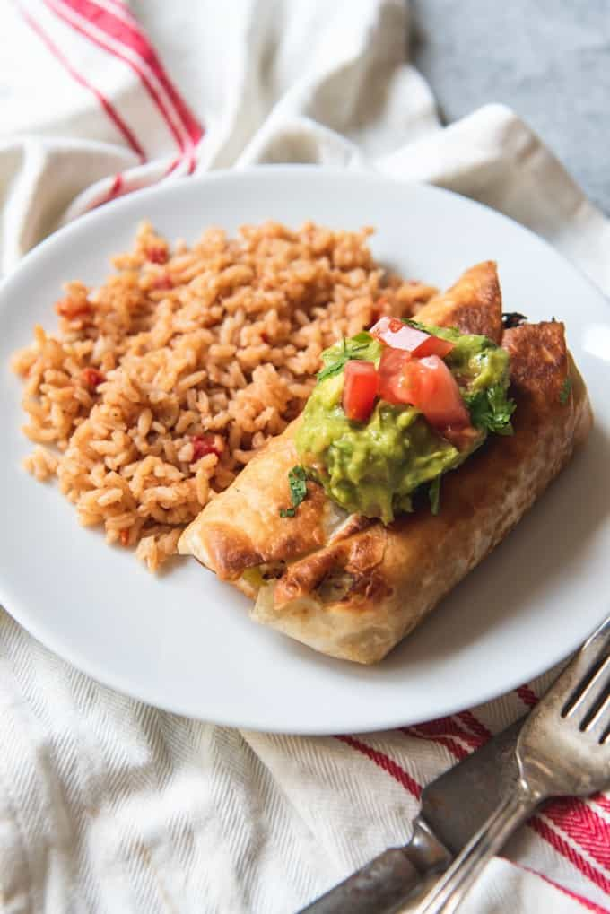 a green chili chicken Chimichanga with green guac and tomatoes on top next to a side of red rice
