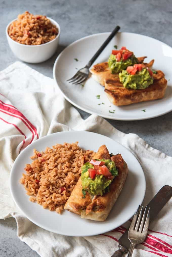 two white plates with Chimichangasandadded garnish of guacamole and diced tomatoes