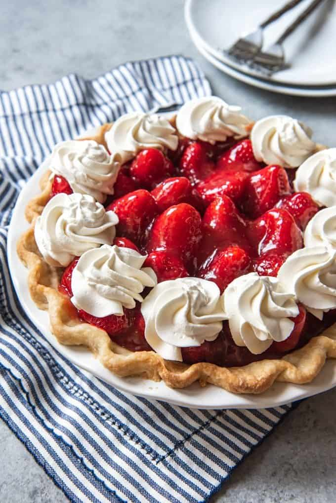 An image of a homemade strawberry pie topped with dollops of fresh whipped cream.