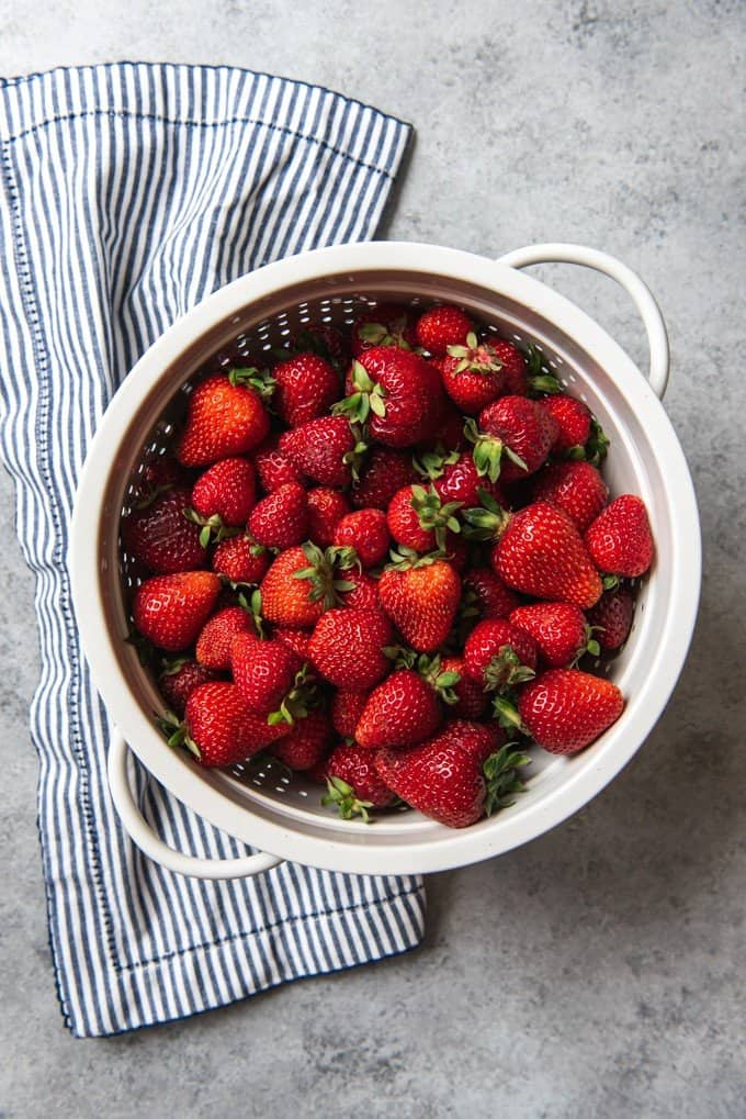 An image of a white colander filled with fresh strawberries.