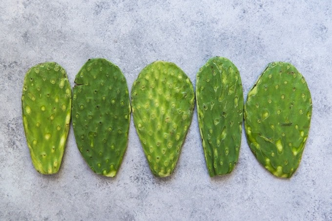 An image of five prickly pear cactus paddles, also known as nopales, trimmed of spines for grilling.