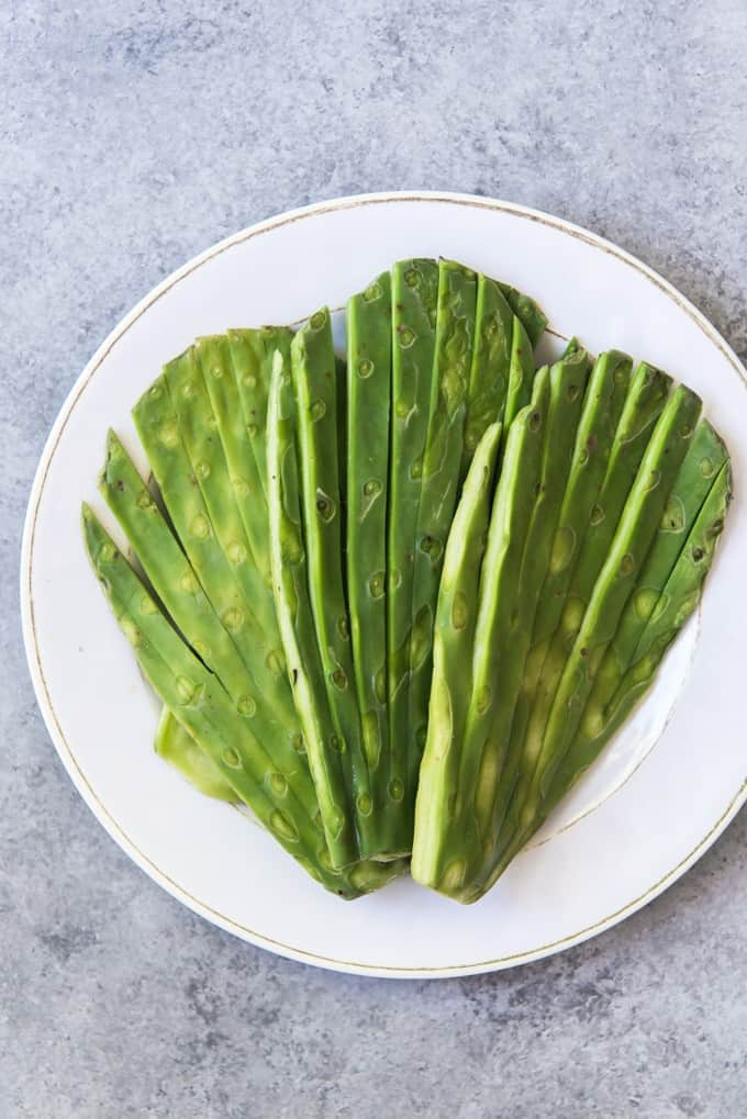 An image of cleaned and trimmed nopales, aka prickly pear cactus paddles, sliced into fans for easy grilling.