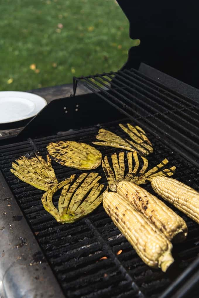 An image of cactus paddles (nopales) and corn on the cob cooking on a grill.