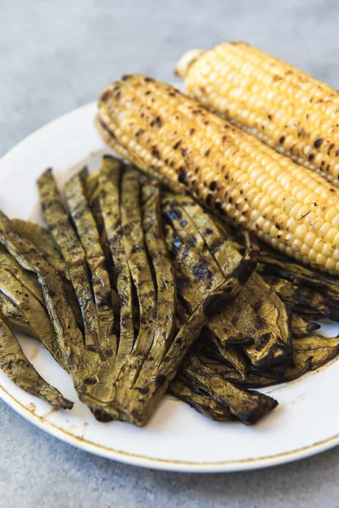 An image of grilled cactus paddles (also known as nopales) and corn on the cob.