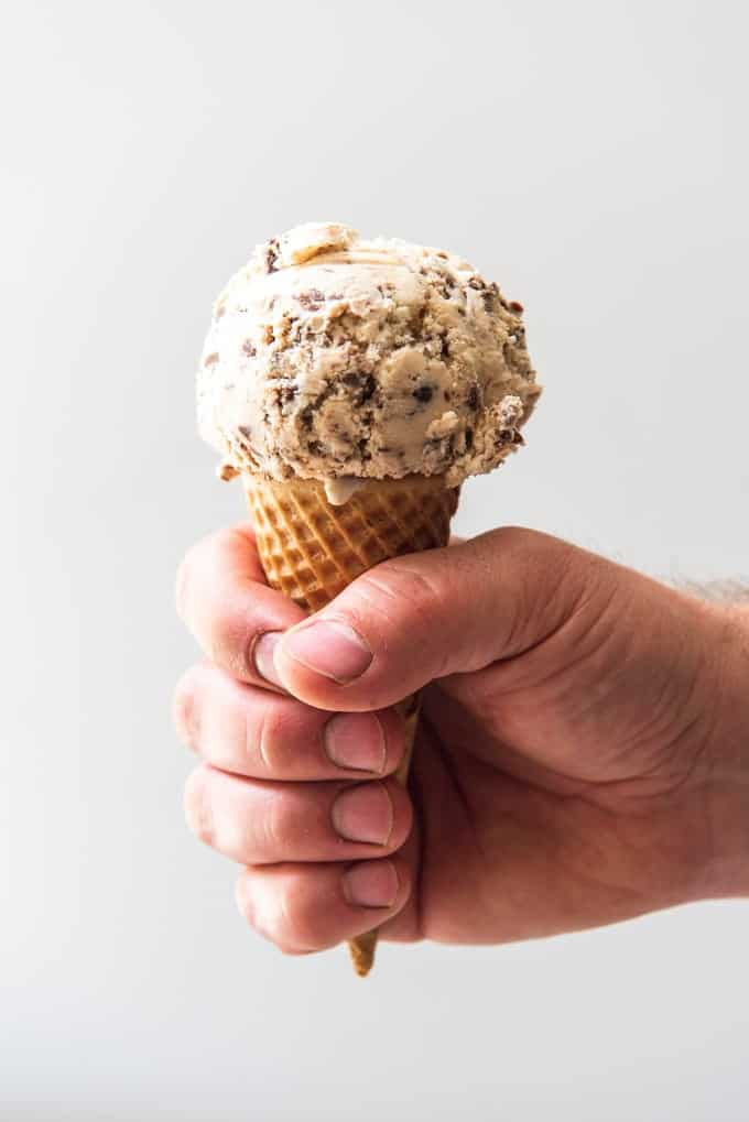 An image of a hand holding a sugar cone with a scoop of Nutella Swirl Ice Cream on it, inspired by our favorite flavor of gelato in Italy.