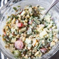 a glass bowl filled with creamy summer corn salad