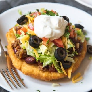 Deliciously crispy on the outside, soft and chewy on the inside, Navajo Tacos made with Indian Fry Bread are topped with a meaty mixture of taco seasoned ground beef and beans, then all the fixings like sour cream, shredded lettuce, cheddar cheese, and tomatoes!