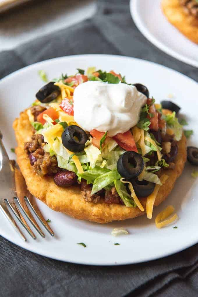 a frybread taco on a white plate next to a fork