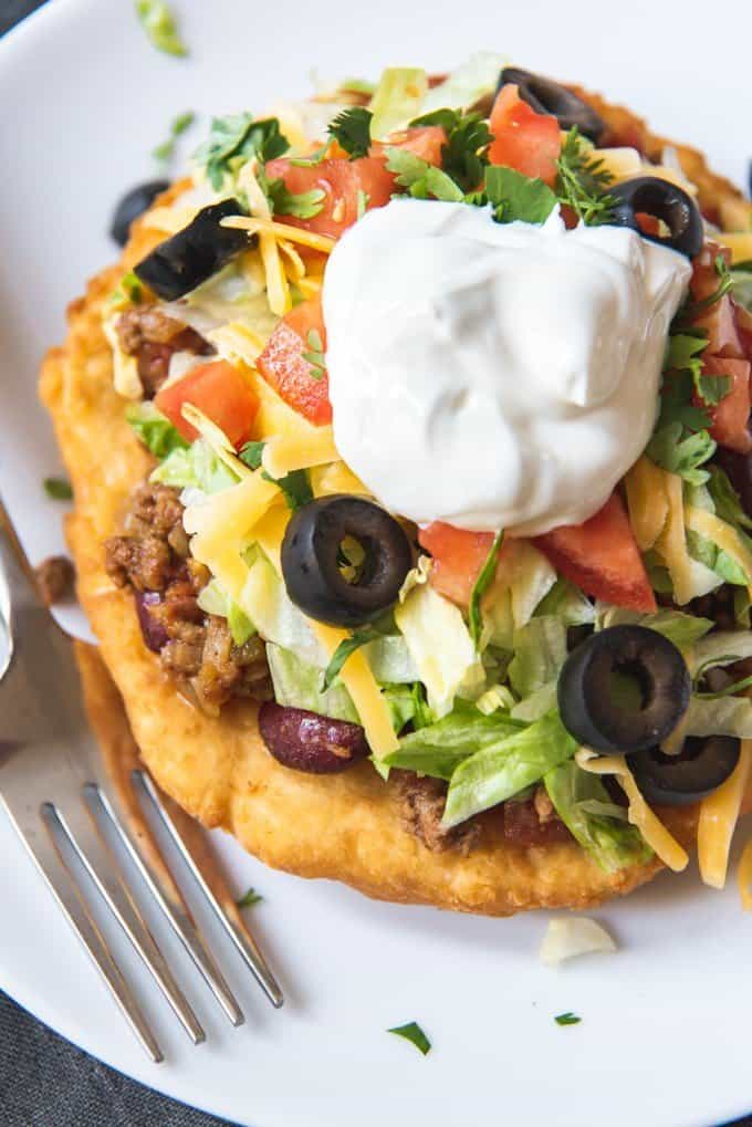 An image of Native American Tacos made with Navajo fry bread, then topped with taco meat, beans, lettuce, tomatoes, cheese, olives, and sour cream.