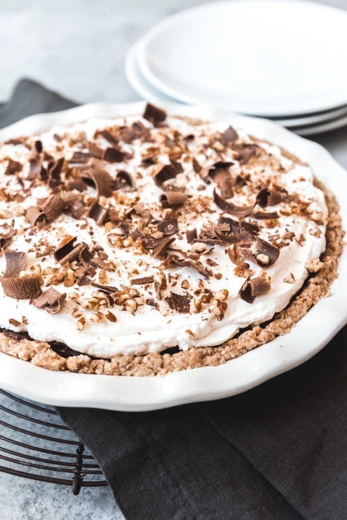 An image of a four-layer delight dessert from Arkansas known as Possum Pie with chocolate shavings and chopped pecans on top.