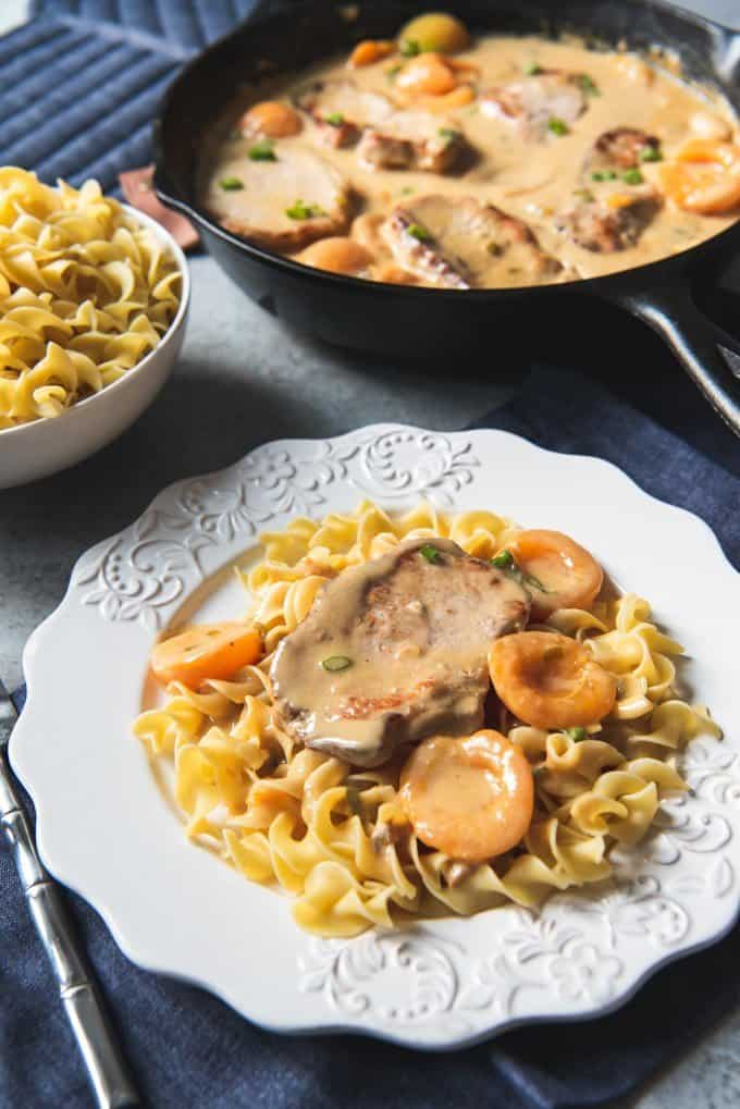 a skillet full of creamy apricot porkchops and a bowl of egg noodles behind a white plate with egg noodles apricots and a pork chop