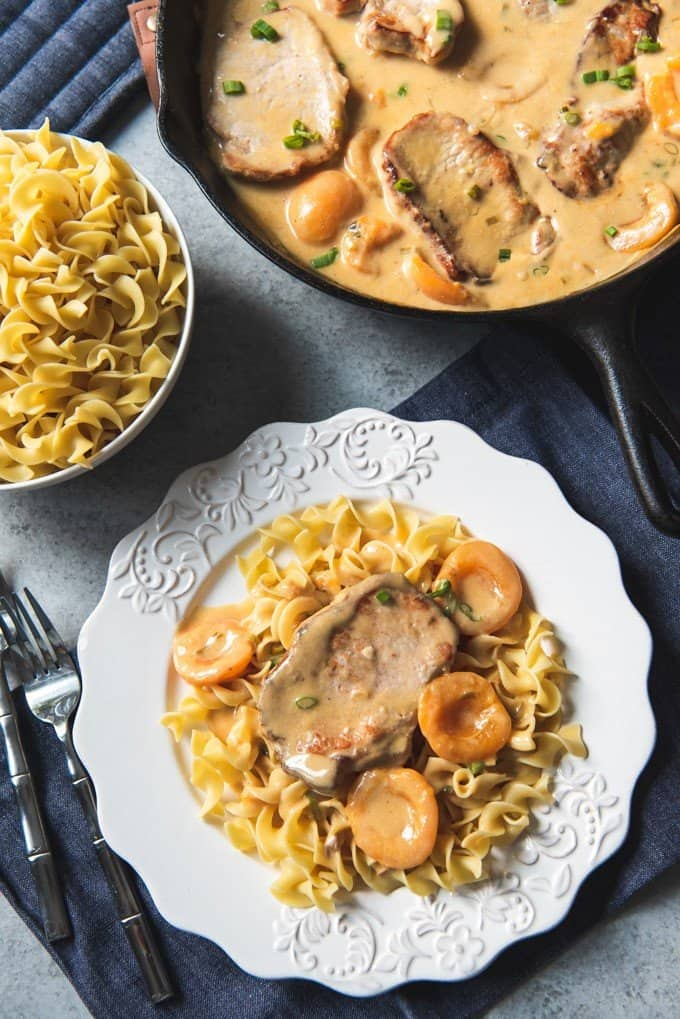 a white plate with egg noodles apricots and a pork chop with a bowl of egg noodles and a skillet of creamy apricot porkchops to the side