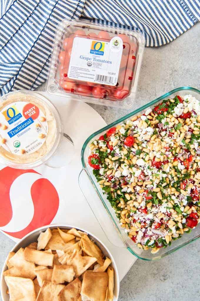 An image of an easy party appetizer recipe for Greek 7 Layer Dip with a bowl of pita chips on the side for dipping.