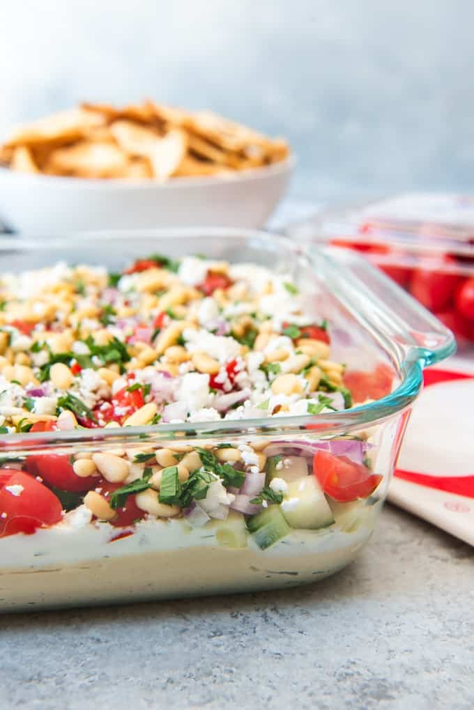 An image of the layers of a Greek 7 layer dip that is an easy appetizer recipe for parties and perfect with toasty pita chips.