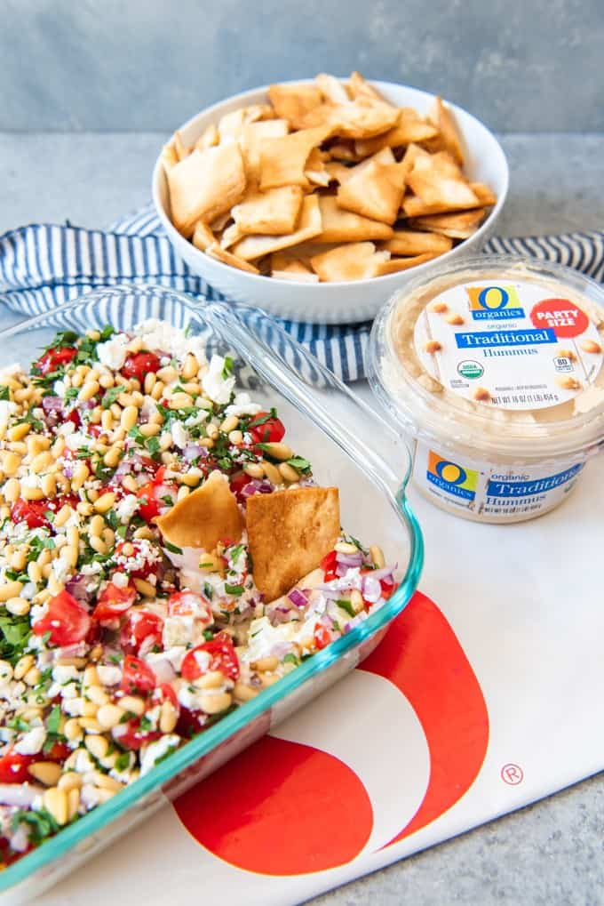 An image of a healthy layered Greek dip with pita chips in a bowl.