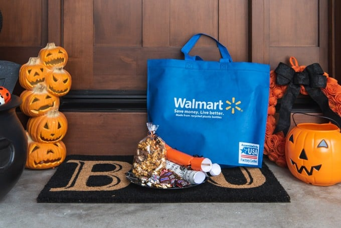 An image of a blue Walmart bag and plate of Halloween goodies in front of a doorstep decorated for Halloween.