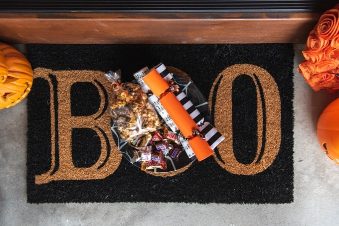 "An image of a Halloween doormat that says ""Boo"" with a plate of treats left to boo friends and neighbors."