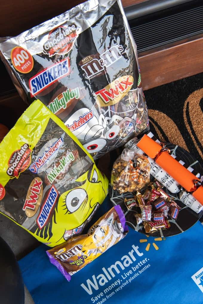 An image of a plate of seasonal candies, homemade Twix caramel corn, and Halloween poppers with big bags of Halloween candy.