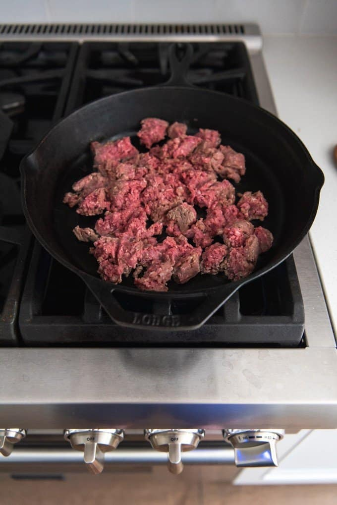 An image showing how to brown ground beef in a cast iron pan.
