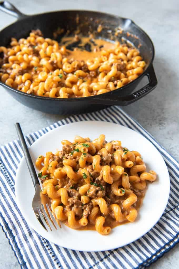 An image of a serving of cheesy pasta with ground beef for homemade hamburger helper made from scratch, with the skillet full of pasta in the background.