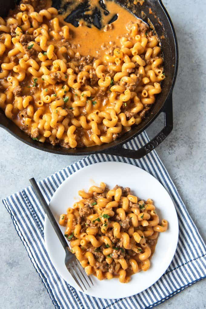 An image of a plate of homemade hamburger helper next to a large skillet used to prepare it.