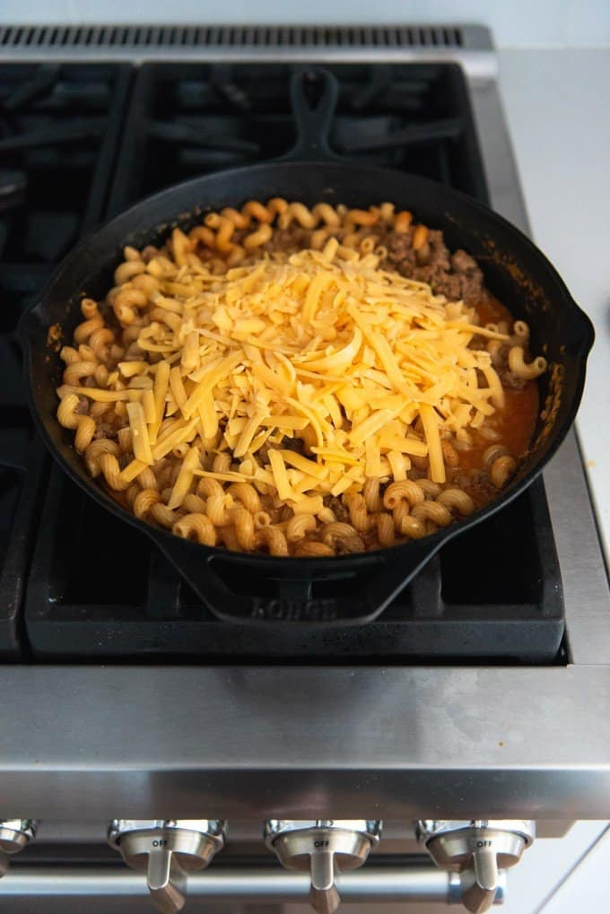 An image of shredded cheese being added to cooked pasta and ground beef in a cast iron skillet.