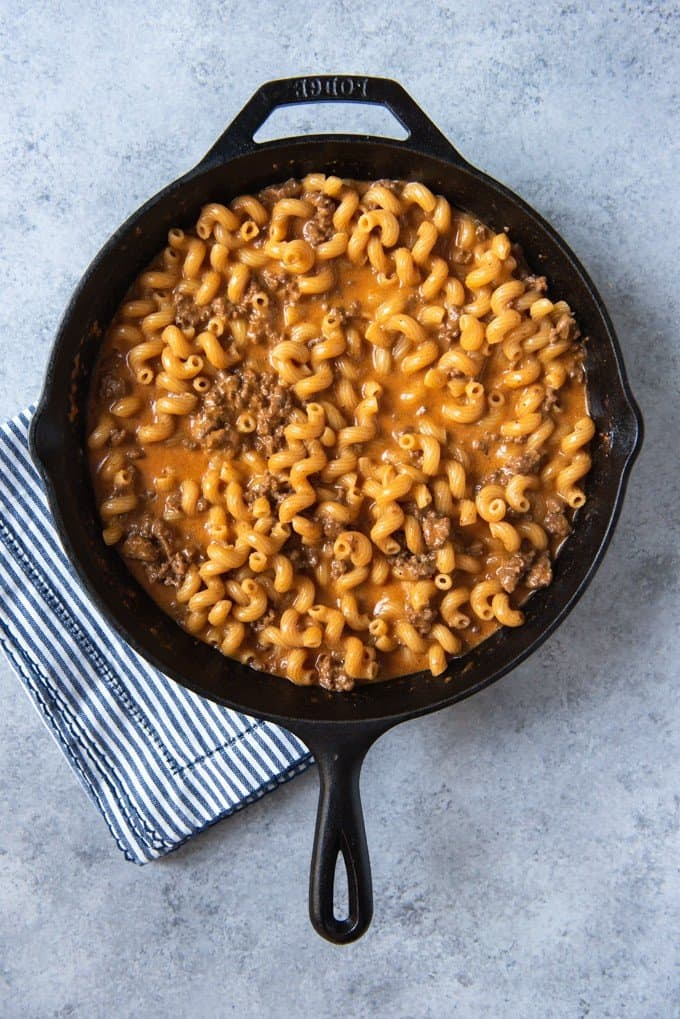 An image of cheesy pasta noodles and ground beef with spices in a pan.