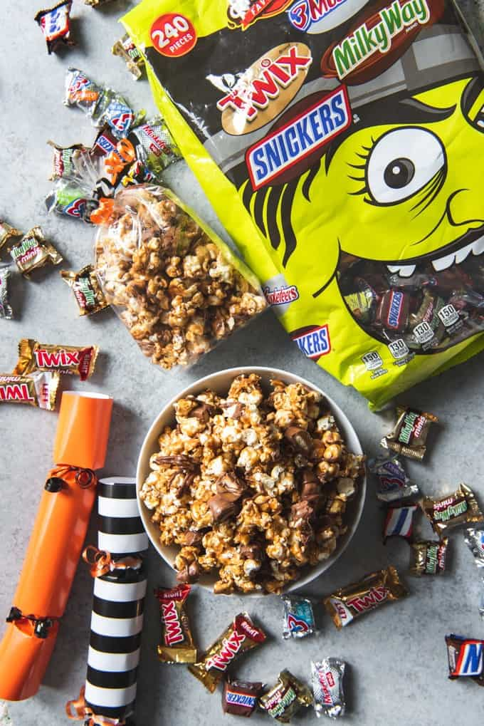 An image of a bowl of Twix caramel popcorn surrounded by Halloween candy and Halloween poppers.