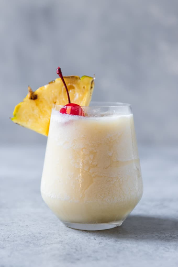 An image of a glass of non-alcoholic pina colada smooothie garnished with a pineapple wedge and maraschino cherry.