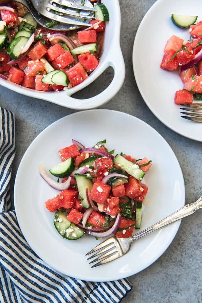 An image of a summer potluck favorite - fresh watermelon salad with feta, basil and cucumbers in a honey lime vinaigrette.