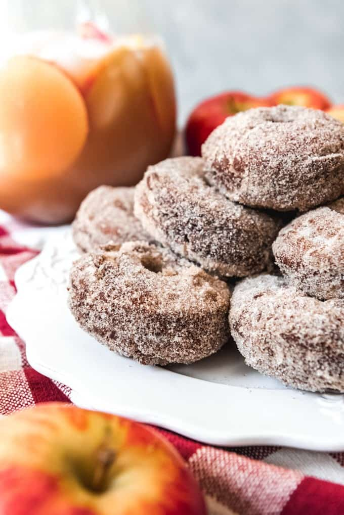 An image of a stack of apple cider doughnuts on a white plate with a pitcher of apple cider and apples in the background.