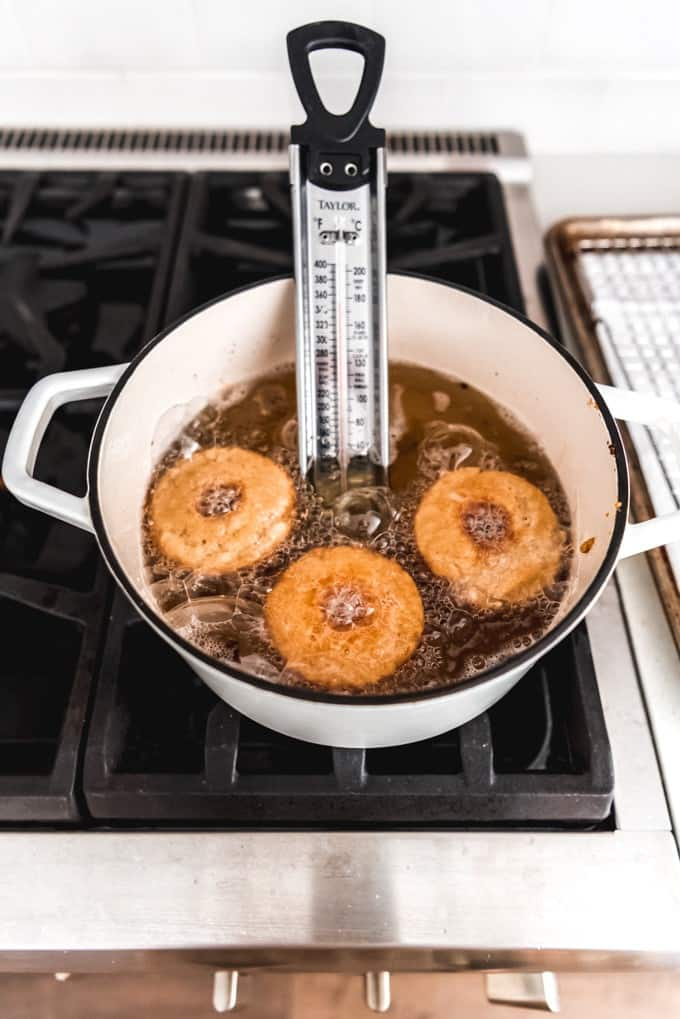An image of apple cider donuts frying in oil on a stovetop.