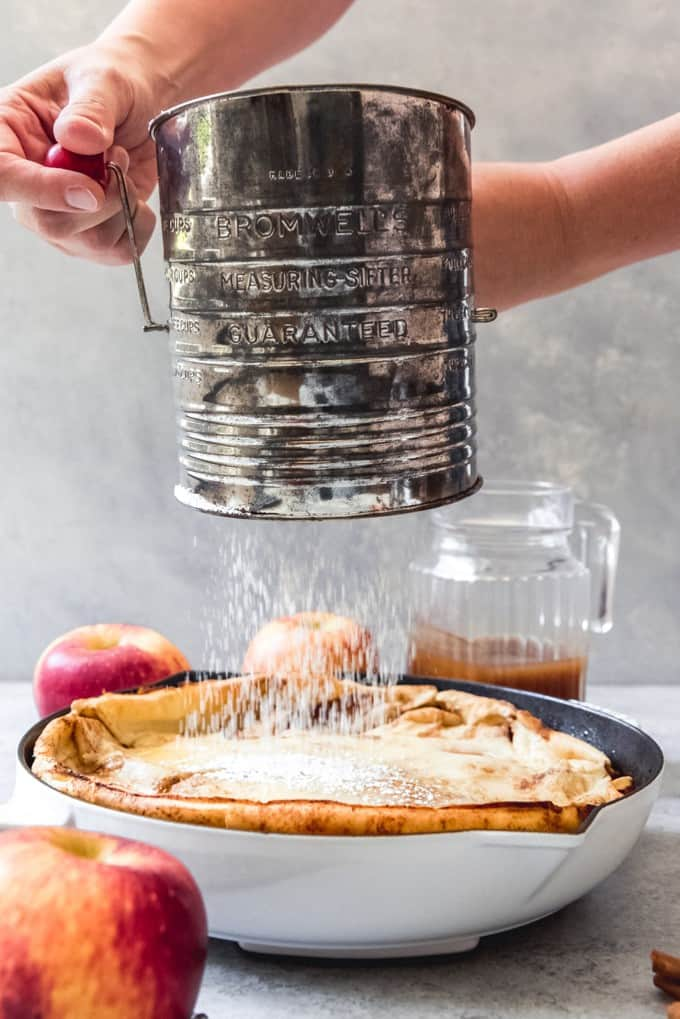 An image of German apple pancakes being dusted with powdered sugar from a sifter.