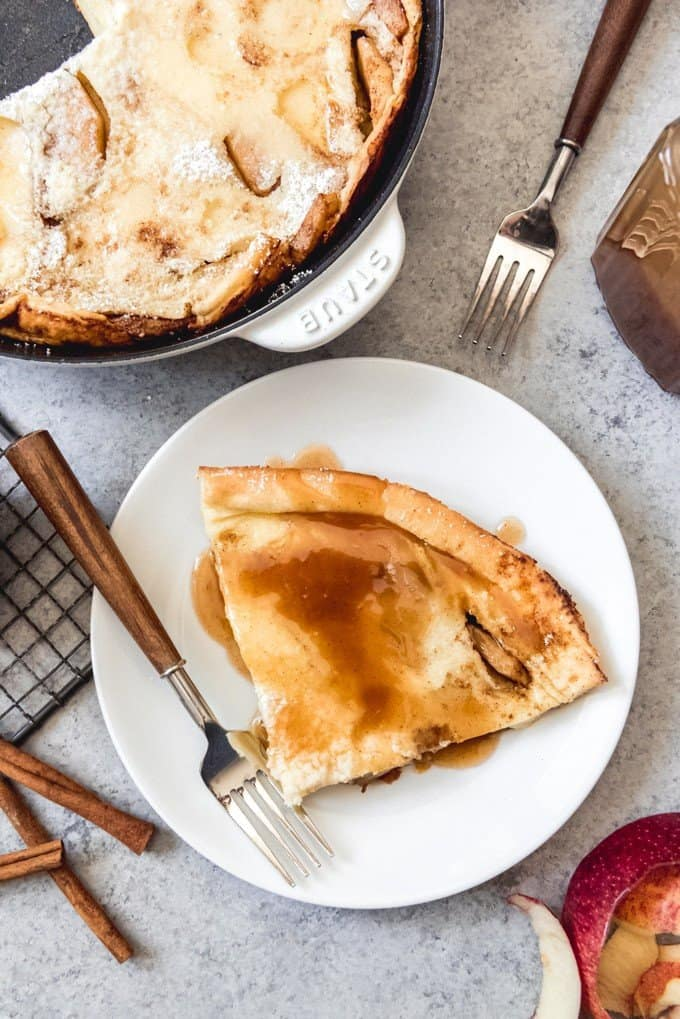 An image of a slice of Apple Dutch Baby Pancake drizzled with cider syrup with the rest of the pancake in a skillet behind it.