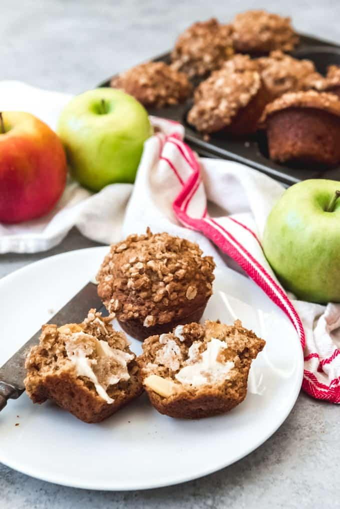 An image of a buttered apple muffin with oat streusel topping on a plate with more muffins and whole apples behind it.