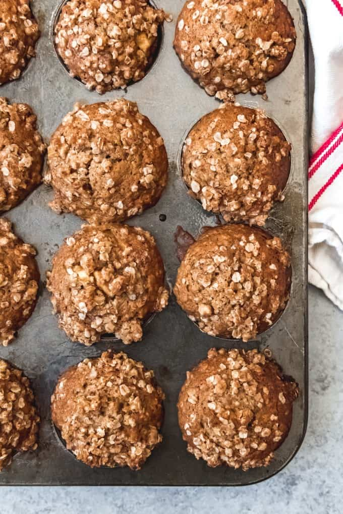 An image of a dozen apple oatmeal muffins, fresh out of the oven.