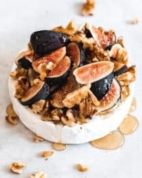 a wheel of baked brie covered in honey and figs and nuts