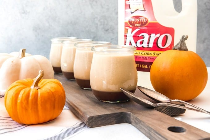 An image of individual servings of pumpkin panna cotta with salted caramel sauce in glass jars next to some pumpkins.